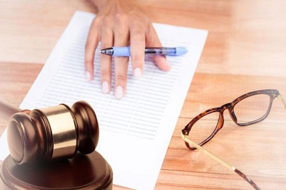 Compuesta digital de martillo en el escritorio con gafas y escritura a mano